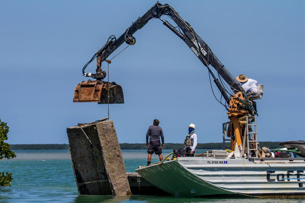 The marine salvage crews lifted the boats off the bottom to carry them in to Key West on the barge.