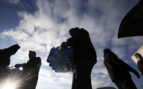 Midwest Food Bank workers and volunteers carry cases of water that was donated, Wednesday, Jan. 27, 2016, in Indianapolis. All of the water that was collected will be sent to Flint, Mich., where drinking water has been contaminated by lead. (Darron Cummings/AP)