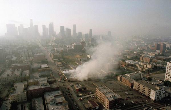 Smoke rises from a shopping center burned by rioters early Thursday morning on April 30, 1992, as the Los Angeles skyline is partially obscured by smoke. (Paul Sakuma/AP)