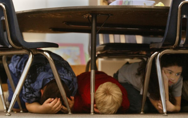 <p>First graders from left, Sam Moreno, 6, Sean Scott, 7, Jessica Ayaly, 6, hide out under a table during an earthquake drill at St. Mary's Public School in Mt. Angel, Oregon, Thursday, Sept. 26, 2002.</p>