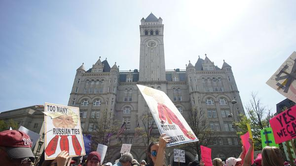 Protestors demonstrating April 15 against President Trump's purported ties to foreign governments walk by the Trump hotel during in Washington, D.C.