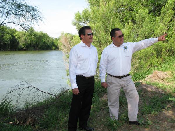 Alberto Perez, administrador municipal de Rio Grande City (izquierda), y Gilbert Millan, director de planificación de la cuidad, caminan a lo largo de la ribera del río para mostrar la poca distancia a la que la cerca planeada estaría del agua.