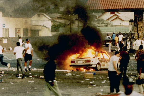 A car burns as looters take to the streets at the intersection of Florence and Normandie avenues — considered the flashpoint of the LA riots — on April 29, 1992.