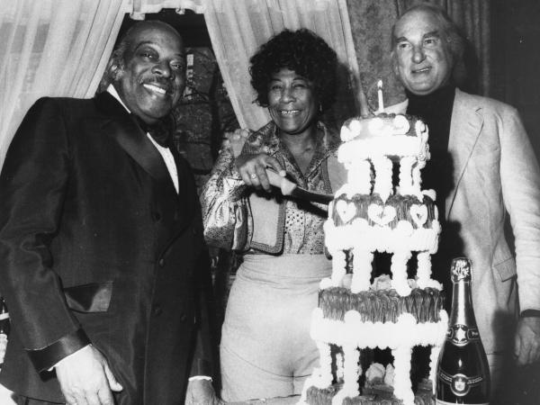 Jazz pianist and band leader William Basie, better known as Count Basie, with manager Norman Granz (right) to celebrate the 54th birthday of Ella Fitzgerald.