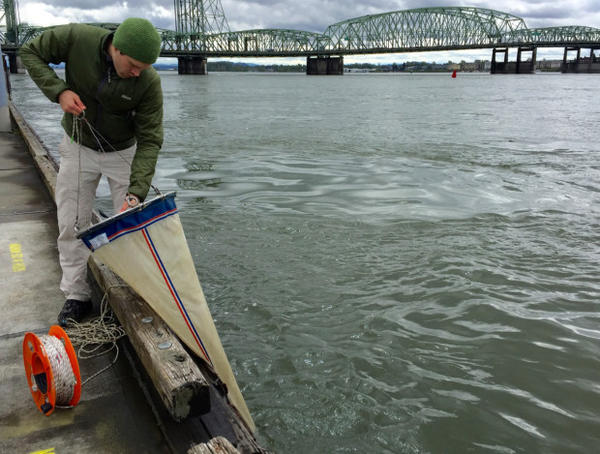 <p>Eric Dexter collects microscopic plankton samples from the Columbia River using a very fine filter.</p>