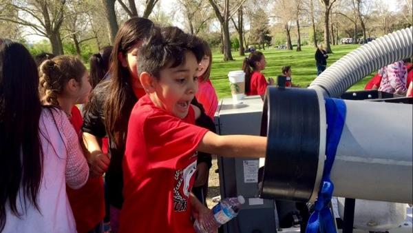 <p>Victor Susunaga Castellanos, a fourth-grader at Westgate Elementary School, puts his hand inside the salmon cannon. The salmon cannon sucks fish up and over obstructions — like dams.</p>