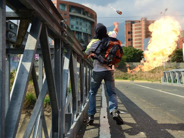 A protester tosses a combustible device during a clash with riot police in Caracas on Wednesday.