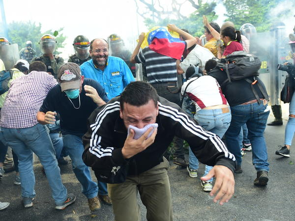 A demonstrator protects his mouth with a cloth as riot police advance on protesters on Wednesday. Security forces fired tear gas and water cannons at protesters during the Caracas rally, while protesters often returned fire with rocks and other objects.