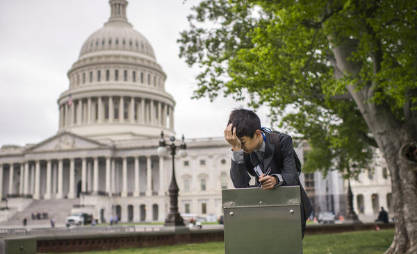 A student from Wisconsin takes a break in front of the Capitol Wednesday. Republican and Democratic negotiators appear ready to pass a one-week funding measure to keep the government open.