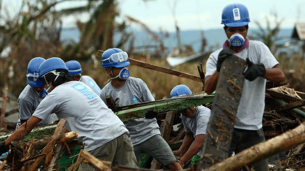 Locals working for a UNDP cash-for-work program clear debris in one of the neighborhoods worst affected by the typhoon that hit Tacloban, Philippines, last November. Tim Walsh runs the program, which he hopes will help keep the local economy going.