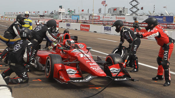 Crew chief Donny Stewart, far right, throws his air gun back towards the wall at the end of a pit stop at the Firestone Grand Prix of St. Petersburg, Fla.