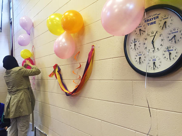 A volunteer at the the Dar-ul-Islam mosque in Elizabeth, N.J., prepares for a party to welcome refugees. More than 50 newly arrived Syrian women and children were invited to the party.