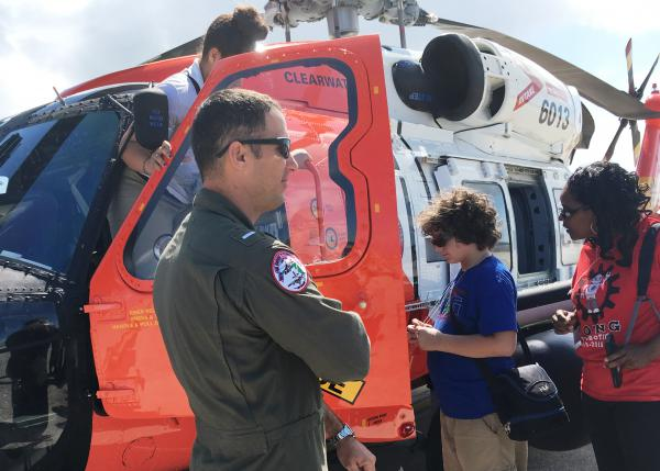 "Coast Guard pilot Justin Neal supervises students as they climb into the cockpit to take ""selfies."""