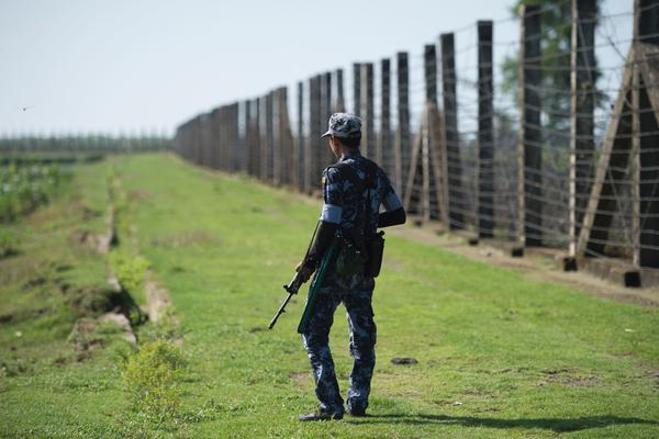 An armed Myanmar border guard patrols the fence along the river dividing Myanmar and Bangladesh in Myanmar's Rakhine state, on Oct. 15, 2016. The government says Rohingya militants carried out border raids that month that killed nearly a dozen policemen.