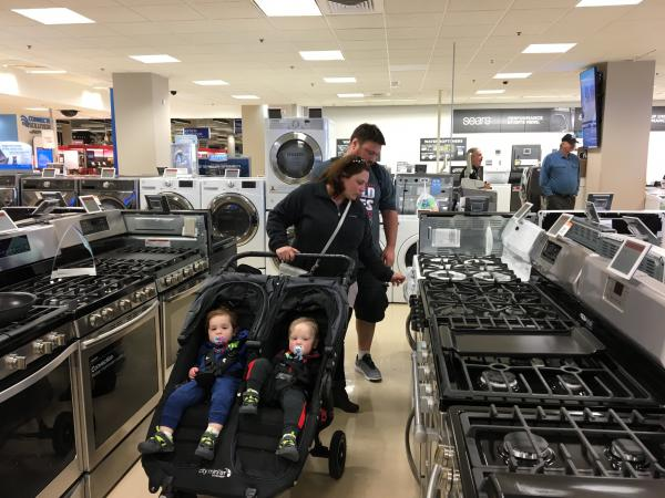 Carla and Jeremy Lang push their twin 18-month-old sons in a stroller while looking at ovens and stoves at a Sears northwest of Chicago.
