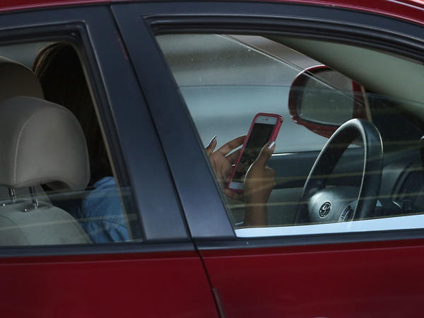 A driver uses a phone while behind the wheel of a car on April 30, 2016, in New York City.