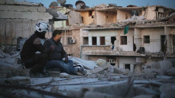 "Two members of ""The White Helmets"" pause to take stock in the documentary <em>Last Men in Aleppo.</em>"