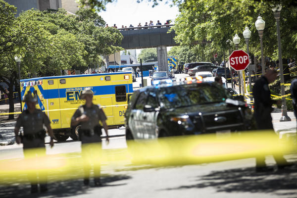Emergency services personnel respond to the scene outside Gregory Gym where four students were stabbed, one fatally.