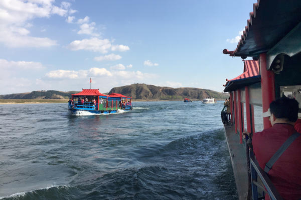 Chinese tourists ride ferryboats to the North Korean side of the Yalu River.