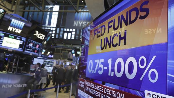 A television screen on the floor of the New York Stock Exchange reflects the Federal Reserve's decision Wednesday to hold rates steady.