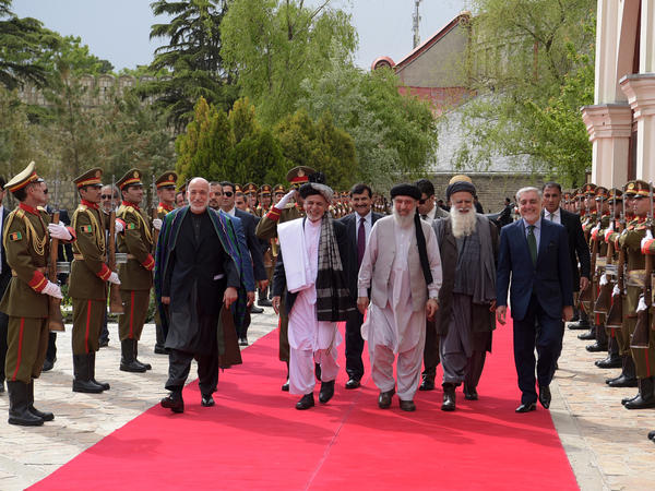 From left to right, former Afghan President Hamid Karzai and current President Ashraf Ghani walk with Gulbuddin Hekmatyar, former mujahideen leader Abdul Rasul Sayaf and Afghanistan's Chief Executive Abdullah Abdullah to a special ceremony for Hekmatyar's return at Kabul's presidential palace on May 4.