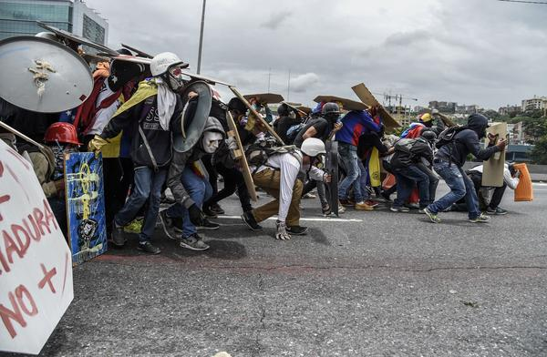Hooded demonstrators equipped with helmets, gas masks and makeshift shields face off against riot police during a protest in Venezuela's capital, Caracas, on Wednesday.