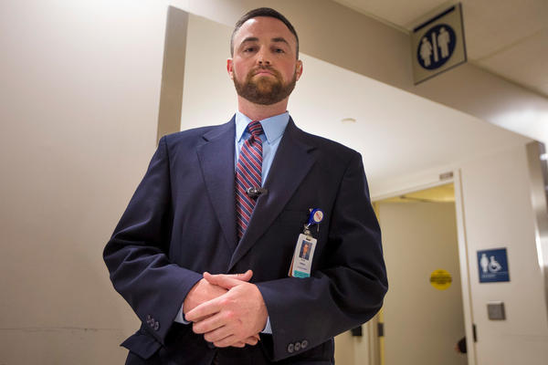 Ryan Curran, the day shift operations manager of police and security at Massachusetts General Hospital, stands in front of the bathrooms in the main lobby.