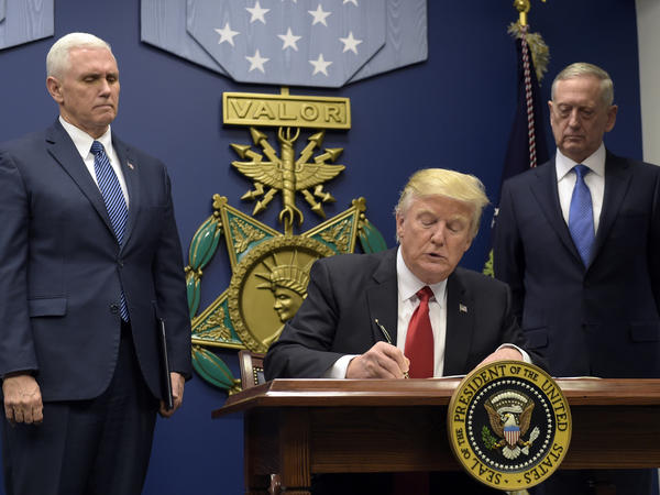 President Trump, with Vice President Pence (left) and Defense Secretary James Mattis (right) watching, signs an executive action on extreme vetting at the Pentagon on Jan. 27.
