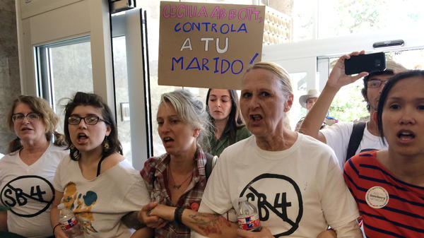 Protesters rally during a sit-in at the Texas Department of Insurance building in Austin last week. They oppose the bill that Gov. Greg Abbott signed into law Sunday. It compels police to enforce federal immigration laws.