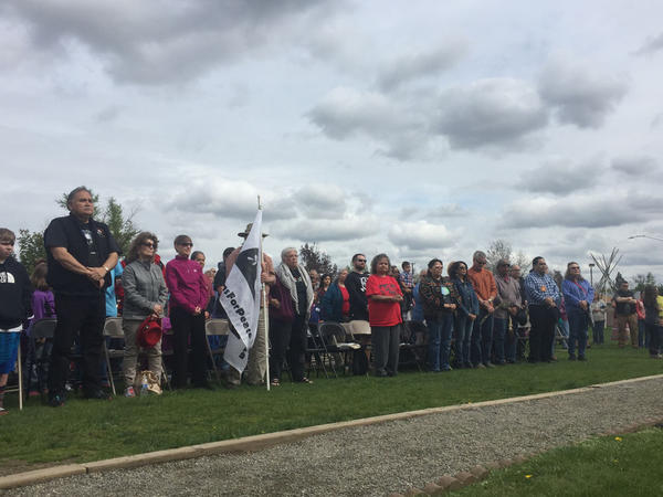 More than 100 people including community leaders and Native elders gathered outside the Salish School of Spokane Saturday afternoon after racial slurs were discovered scrawled on classroom walls Friday morning.