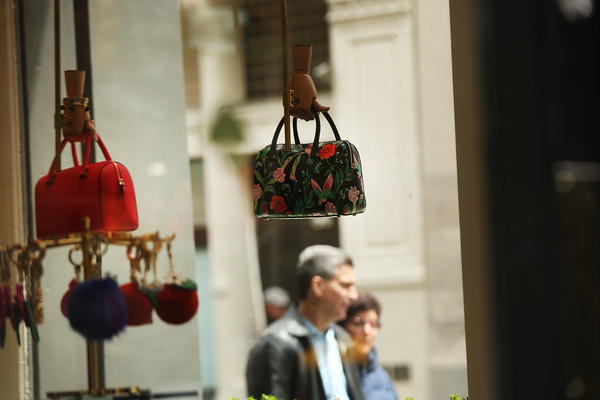 "Purses hang in the window of a Kate Spade store in New York City's SoHo neighborhood. The $2.4 billion deal with Coach aims to ""create the first New York-based house of modern luxury lifestyle brands."""