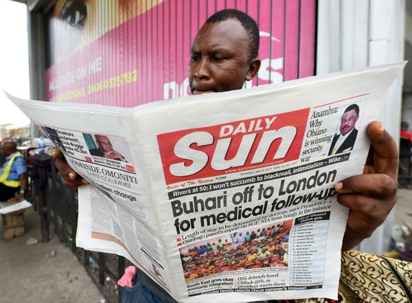 "A Nigerian man in Lagos reads a newspaper addressing President Mohammadu Buhari's ""follow-up medical consultation"" in London."