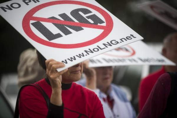 <p>Protesters use signs to shield themselves from the rain during a rally before the Oregon LNG permit public hearing.</p>