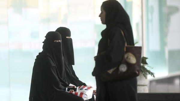 Female shoppers in traditional Saudi Arabian dress wait for their transport outside the Kingdom Centre shopping mall in Riyadh. Women's decision-making abilities are limited by the country's guardianship rules.