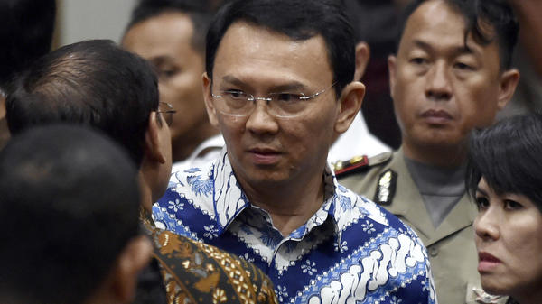 "Jakarta Gov. Basuki ""Ahok"" Tjahaja Purnama (center) talks with his lawyers after his sentencing hearing Tuesday in Indonesia's capital city."
