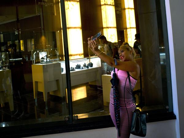 A Cuban girl takes a selfie in front of a window of a luxury store at the Manzana de Gomez Kempinski five-star hotel in Havana on Monday. The Manzana de Gomez Kempinski bills itself as Cuba's first real five-star hotel, and the brand-name shops around it appear designed to reinforce that.