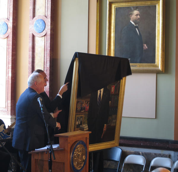 Gov. Pat Quinn removes a cloth to reveal his official portrait in the Illinois Statehouse. He did so under the portrait of former governor John Peter Altgeld (1893-1897), coincidentally another Democrat who was defeated in an attempt at reelection.