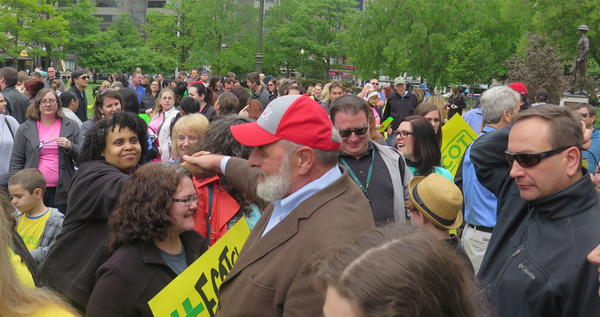 ECOT founder Bill Lager shakes hands walking through the crowd.