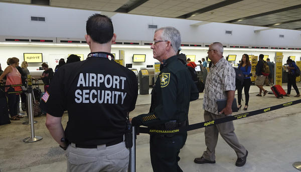 Airport Security and a Broward Sherriff's Deputy keep an eye on the line at Spirit Airlines, Tuesday, May 9, 2017, at the Fort Lauderdale-Hollywood International Airport in Fort Lauderdale, Fla.