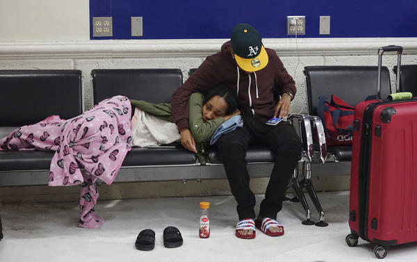 Latreece Smith rests as her friend Tamari Cameron checks flight information, Tuesday, May 9, 2017, at the Fort Lauderdale-Hollywood International Airport in Fort Lauderdale, Fla. Skirmishes involving irate passengers broke out on Monday.