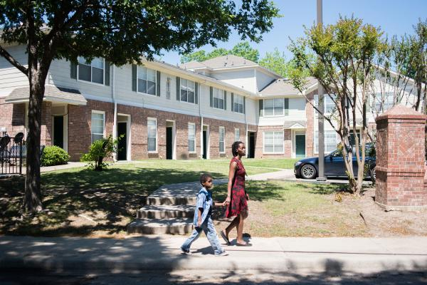 Farryn Giles and her son Isaiah, 6, walk in their east Dallas neighborhood. While she received a Section 8 voucher to help them move to a neighborhood with more opportunities, finding an apartment that would take the voucher was challenging.