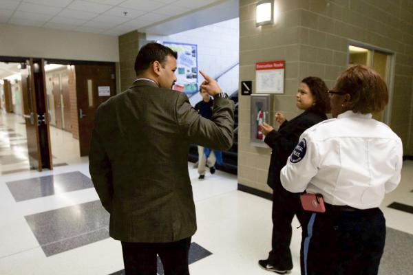 Rayamaji discusses testing logistics with a teacher and security officer.