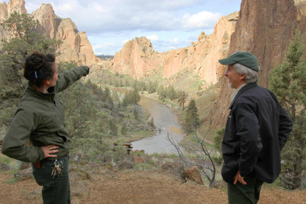 <p>Ranger Josie Barnum and park director Scott Brown survey the valley in Smith Rock State Park. The park already sees crowds of at least 2,000 visitors on a weekend day. During the solar eclipse, there could be double or triple the visitor volume.</p>