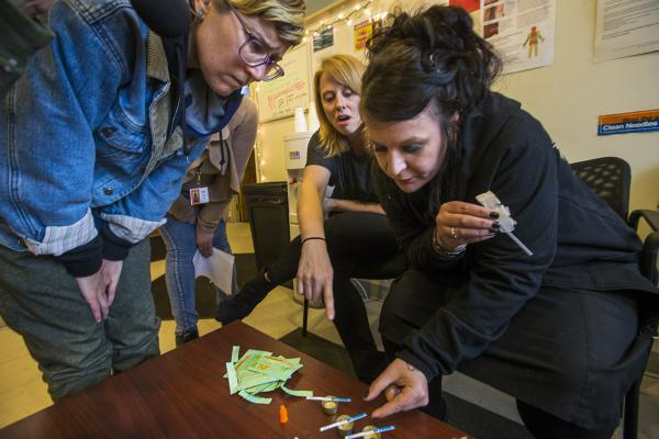 Jess Tilley, right, gives a demonstration with her fentanyl test strips. At left is needle exchange worker Emily Moulton and in the center is Liz Whynott, Tapestry Health's director of HIV health and prevention. (Jesse Costa/WBUR)