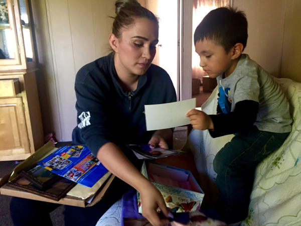 <p>Sally Garcia Acosta shows her son Daniel, 3, photos of his sister. Maria Rosario Perez died from anencephaly, which is affecting three Eastern Washington counties at four times the national average.</p>