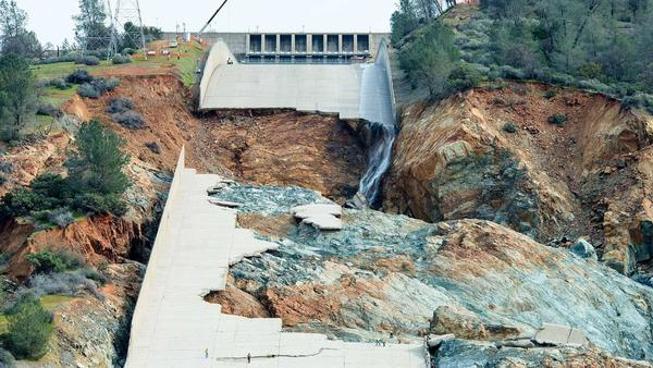 """Ruins of the main spillway at Oroville Dam reveal a blend of """"fresh"""" (blue-gray) rock and """"weathered"""" (reddish-brown) rock underneath. (Calif. Dept. of Water Resources)"""