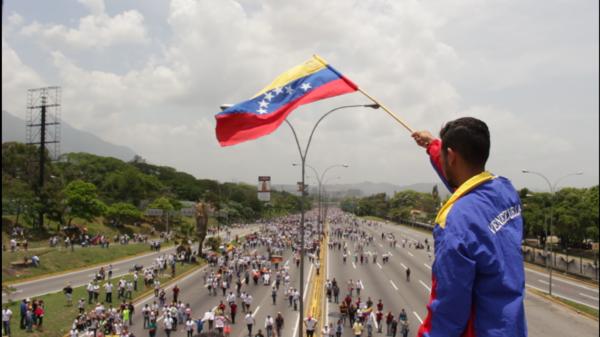 Wuilly Arteaga waves the Venezuelan flag as demonstrators gather below.
