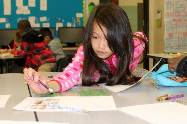Trish Nguyen works on a graph in a second-grade classroom at Confluence Academy South City.