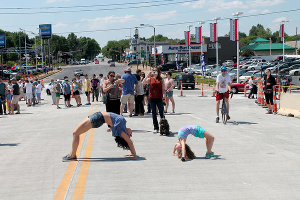 Amy Johnson and Dahlia Goldstein-Larocco, 7, do a yoga pose known as the bridge during the grand reopening of the Kingshighway Bridge.