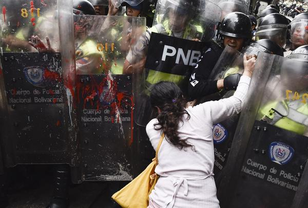 A protester pushes into a phalanx of riot police Friday in Caracas, Venezuela. Demonstrators blame President Nicolas Maduro for the country's economic crisis, food shortages and indefinitely delayed elections. More than three dozen people have died in a month and a half of protests.
